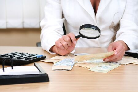 Woman with a magnifying glass in her hands verifies the authenticity of the bill. Calculator, cash money at the desk. Light background