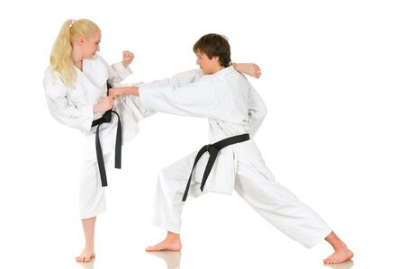 Beautiful young girl and a young cheeky guy karate are engaged in training in kimono on a white background. Competition preparation concept. Copyspace Stock Photo