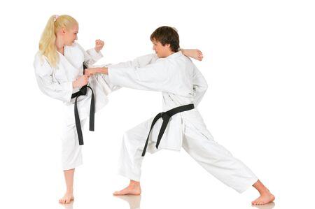 Hermosa joven y un joven chico descarado de karate se dedican a la formación en kimono sobre un fondo blanco. Concepto de preparación de la competencia. Copyspace Foto de archivo