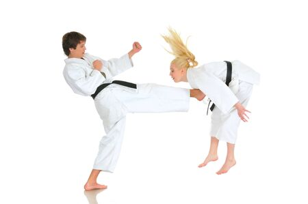 Cute blonde girl and a young cheeky guy karate are engaged in training in a kimono on a white background. Young couple of athletes getting ready for a performance. Copyspace