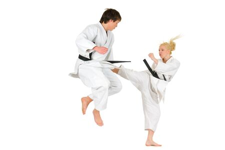 Cute blonde girl and a young cheeky guy karate are engaged in training in a kimono on a white background. Young couple of athletes getting ready for a performance. Copyspace Imagens