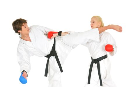 Young karateka students in white kimono black belts in combat gloves train to practice blows with kicking and hands on a white background. Professional sports concept. Advertising space