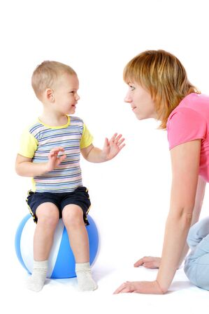 Funny little caucasian white boy sits on blue Inflatable ball. Toddler plays with mother. Childhood. Isolated on light background