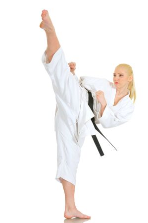 Young talented girl blonde professional karate athlete in a kimono suit with a black belt shows a kick and a good stretch on a white background. Advertising space