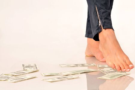 Dollar banknotes on floor under woman legs to imply the fall or devaluation of dollar bills currencies. Isolated on white background