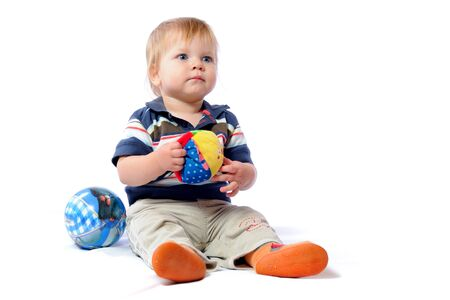 Little toddler plays with loved toy. Boy holding plush ball in hand. Playing with child car. Isolated on white background