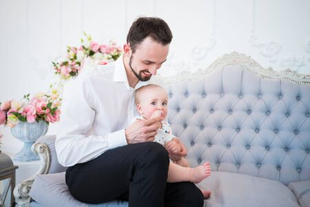 Young handsome man with a beard in formal clothes is holding on the arms of a small restless child sitting on a sofa in a chic interior. Father care concept