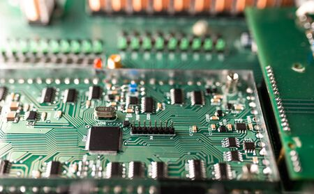 Close-up a large green microcircuit and luminous panels are found in a radio parts factory. Complex electronic equipment concept in a factory