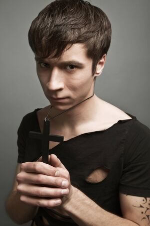 Young man in modern black clothing and freedom tattoo holding big black cross in hands with eyes closed.