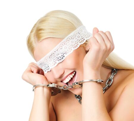 Handcuffed naked blond woman with white lace bandage to close eyes and with chains around the neck. Isolated on light background Stock Photo