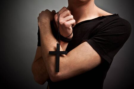 Young man in modern black clothing and freedom tattoo holding big black cross in hands with eyes closed. Beauty and fashion lifestyle concept