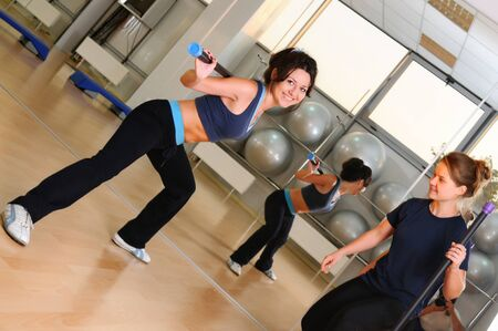 Attractive sportive girls in sportswear doing physical exercise with gym stick. Woman squats with fitness equipment. Sport club interior on background