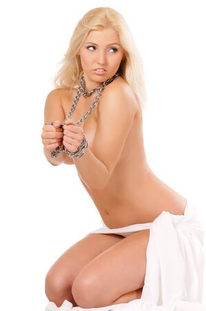 Handcuffed beautiful naked blond woman sitting in underwear with chains around the neck. Isolated on light background