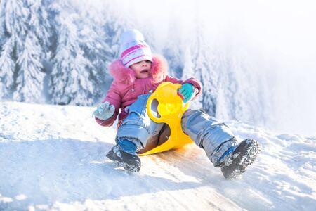 Gelukkig klein meisje in winterkleding bergafwaarts rijden op sneeuw met winter besneeuwde bos op de achtergrond op ijzig heldere dag. Winter familie activiteiten concept