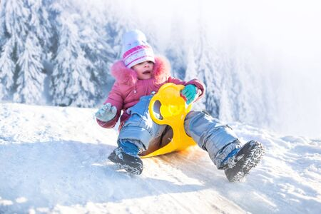 Happy small girl in winter clothing riding downhill on snow with winter snowy forest at background on frosty clear day. Winter family activities concept
