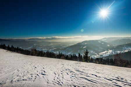 Vista dall'alto di una spaziosa pista da sci innevata sullo sfondo di colline ricoperte di alberi in una gelida giornata invernale di sole. Concetto di vacanza sugli sci. Copyspace