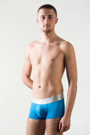 Young caucasian man model in orange mens underpants standing and looking at camera over light background in photo studio. Bright mens underwear concept