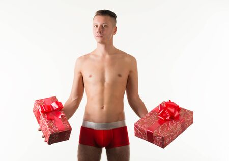 Young caucasian man model in red mens underpants standing and holding present boxes in hands over light background in photo studio. Bright mens underwear concept Banque d'images