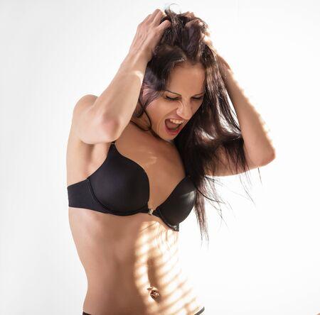 Attractive emolional female model is shaking head with brunette hair in studio wearing black transparent lingerie Zdjęcie Seryjne