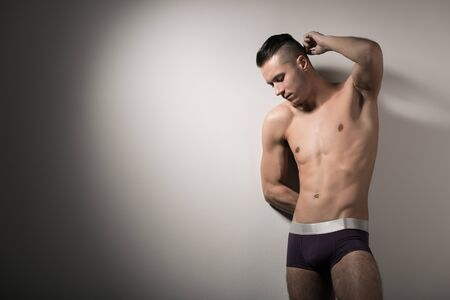Young strong caucasian man model in brown underpants standing and showing his body over grey background in photo studio. Stylish mens underwear concept