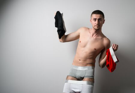 Man in several colorful mens underpants holding underwear in hands over grey background in photo studio. Bright mens underwear concept Stock Photo