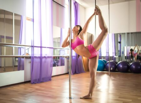 Young slim brunette woman in pink top and shirts standing near pylon in dance studio and stretching her legs on clear day. Modern sexy dance styles concept