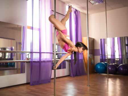 Young slim brunette woman in pink top and shirts hanging on pylon in dance studio and balancing on clear day. Modern sexy dance styles concept Stock Photo