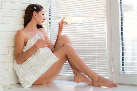 Beautiful slim naked young brunette woman sitting on windowsill and looking at window over white loft wall background. Beauty of woman body and erotic pictures concept Standard-Bild - 134953154
