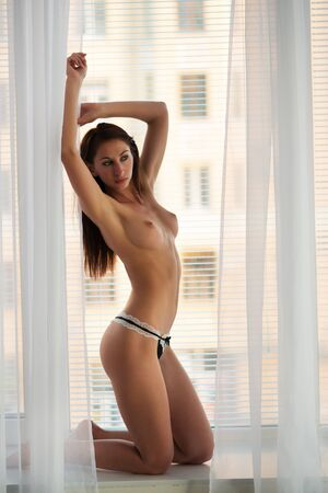Beautiful slim naked young brunette woman sitting on windowsill and looking at window over white loft wall background. Beauty of woman body and erotic pictures concept Stok Fotoğraf