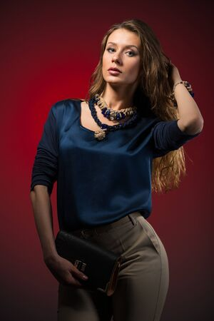 Beautiful young brunette woman in stylish casual clothing with accessories standing over red wall in photo studio. Fashion and beauty concept Zdjęcie Seryjne