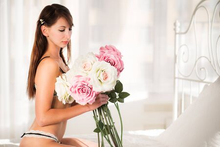 Beautiful slim young brunette woman in black sexy underwear lying in bed and holding flower over white curtain background. Beauty of woman body concept