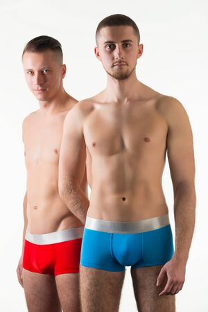 Parts of mens bodies in red and black mens underpants over light background in photo studio. Bright mens underwear concept