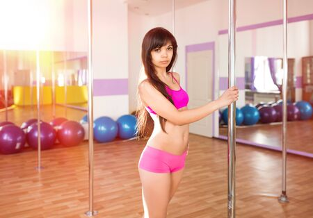 Young slim brunette woman in pink top and shirts standing and holding pylon for dancing in dance studio on clear day. Modern sexy dance styles concept Zdjęcie Seryjne
