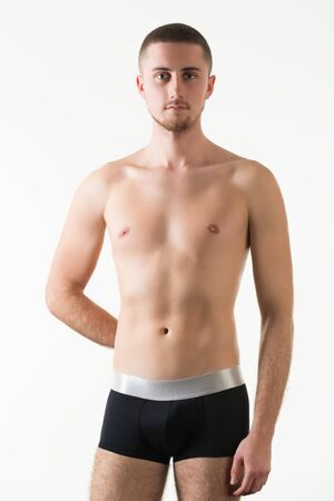Young caucasian man model in black mens underpants standing and looking at camera over light background in photo studio. Bright mens underwear concept