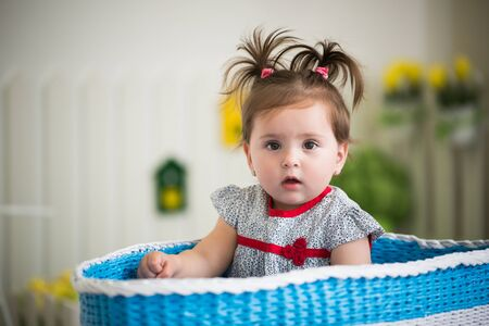 Beautiful little brown-eyed girl sits in a large basket for toys in her cozy children's room. Concept in children's games and activity. Concept of healthy and cheerful little children Reklamní fotografie