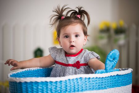 Beautiful little brown-eyed girl sits in a large basket for toys in her cozy children's room. Concept in children's games and activity. Concept of healthy and cheerful little children