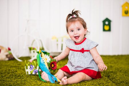 Beautiful cheerful little girl in a dress sits on a rug in her cozy children's room and plays with flowers. The concept of healthy and cheerful preschool children