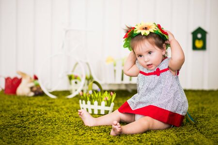 Portrait of curious little barefoot girl in dress and with wreath of flowers on head sitting on rug in cozy children's room. Concept of childrens game and activity. Preschoolers Development Concept 版權商用圖片
