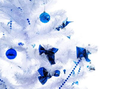 Blue toys hang on a white Christmas tree. Concept of artificial spruce and environmental protection. New Year and Christmas concept and expecting a miracle