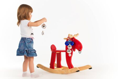 Little charming girl plays with a wooden elk a rocking chair and decorates it New Year's toys on a white background in the studio. Concept of New Year's gifts for children. Advertising space Banco de Imagens