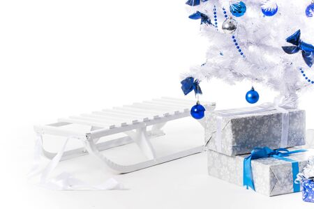 Beautiful New Year sled in silver blue color stand under the Christmas tree on a white background. Concept of artificial christmas tree as environmental protection. Advertising space