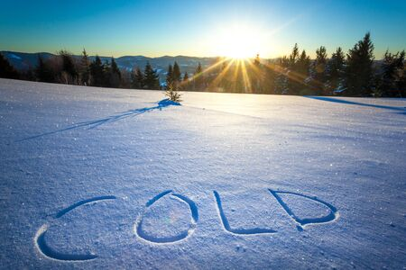 The inscription Cold on snow against the background of the forest and hills on a sunny frosty winter day. The concept of winter time and new year and Christmas Stock Photo