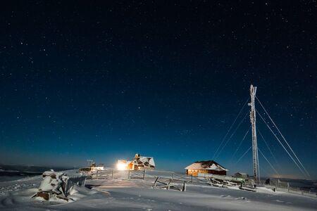 Estación meteorológica o turística con una torre de satélite y un duro país de invierno ubicado en la cima de una colina en una helada noche de invierno contra un cielo estrellado. Lugar para publicidad