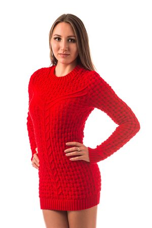 Portrait of a beautiful young slim girl in a red knitted sweater posing on a white background in the studio. Concept of strong warm knitwear. Advertising space Banque d'images - 135487470