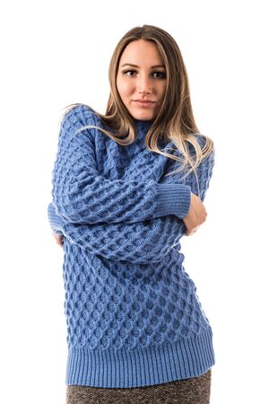 Unidentified stylish young woman in a blue sweater posing on a white background. Concept of warm winter clothes. Advertising space Banque d'images - 135490538