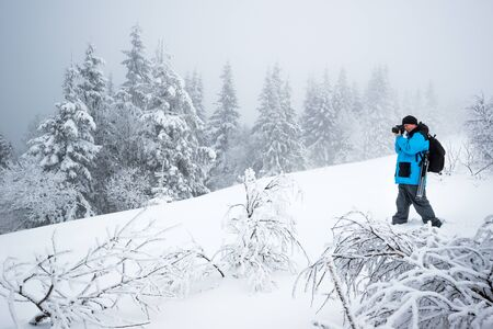 Young male traveler with backpack takes pictures of beautiful tall snowy fir tree in a high snowdrift against the backdrop of fog on a frosty winter day. Trekking and travel concept. Advertising space