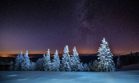 Magical view of the starry clear sky spread over the night ski resort in cloudless cold weather in winter. The concept of unforgettable impressions of a country vacation. Copyspace