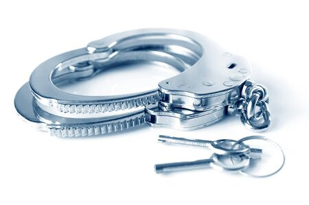 Close-up of metal handcuffs and keys isolated over white background. Sexual games and practicing bdsm concept Banque d'images