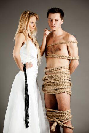 Junge Frau im Hochzeitskleid, die in der Nähe eines Mannes steht, der mit Seilen gefesselt ist