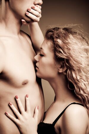 Young woman closing mouth of her partner and biting his nipple